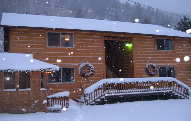 Exterior winter scene with Christmas lights, wreaths, and triming along the deck.  Snowing big flakes.