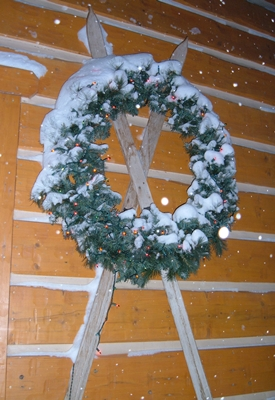 Exterior large Christmas wreath with multi color lights shining, placed over antique skis hanging on the log siding of the condos.  Snow is falling.