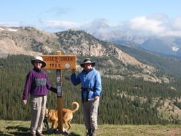Two hikers with a dog at the top of mountain trail.  Snow covered mountains in the distance.
