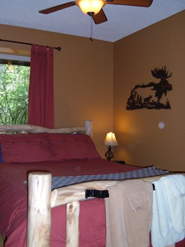 Charming log bed with a red duvet comforter, brown walls, metal art work of a moose on the wall, bed lamp, and a ceiling fan.