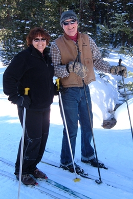 A couple enjoying cross-country skiing on a sunny day.