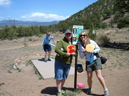 Three ladies playing disc golf outdoors with mountains all around.