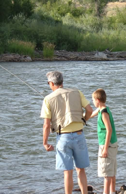 An older man teaching a young man to fly fish along the river bank.