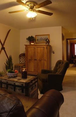 Living room with skis on the wall, antique trunk, armoir, leather sofa, white walls, and a ceiling fan