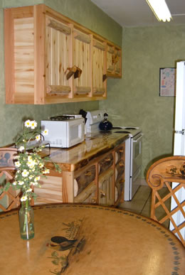 Kitchen with beautiful log cabinets, tile floors, and faux green walls.  Dinning table with faux painting of a rooster