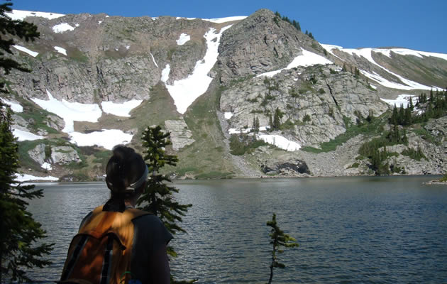 A hiker is looking over a beautiful mountain lake surrounded by snow peak mountains.