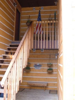 Covered entrance to four condos with hanging pots and the American flag.